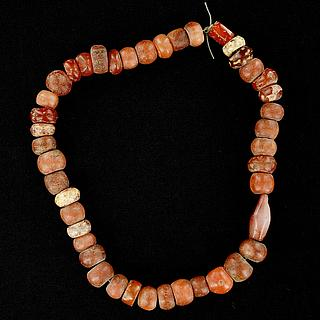 A string of 43 small carnelian beads 05.04.957